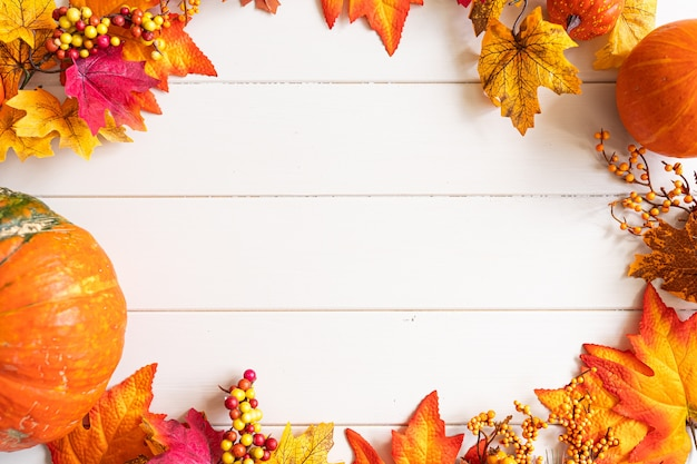Autumn leaves and pumpkins over white wooden background with copy space in center.