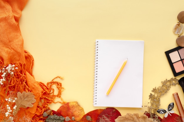 Autumn leaves, scarf, paper notebook and laptop on yellow