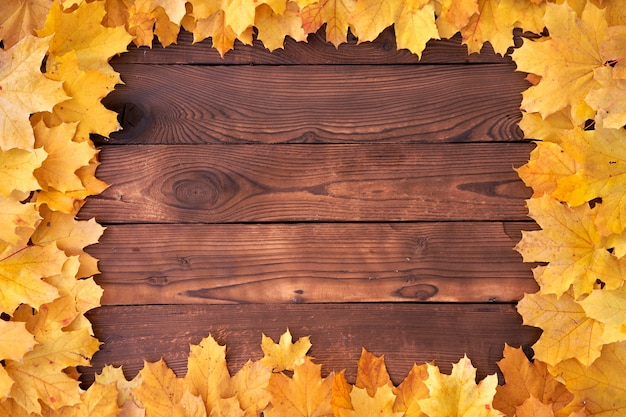 Autumn leaves  square frame on wooden background top view fall border yellow and orange leaves vintage wood table copy space for text
