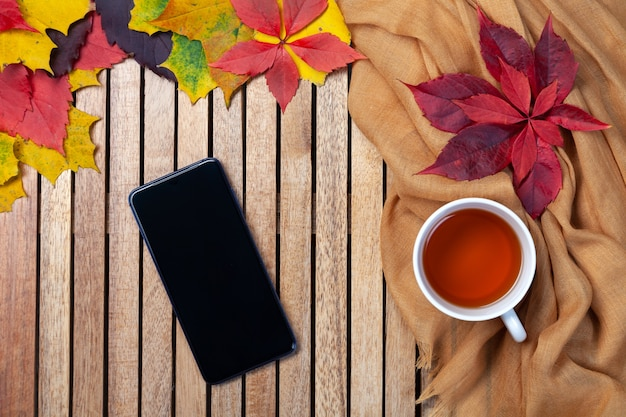 Autumn leaves, tea cup, blank black smartphone screen on table, wooden background