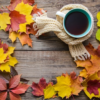 Autumn leaves, tea cup, scarf on wooden background with copy space