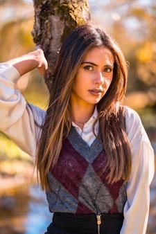가을 라이프 스타일, 젊은 백인 갈색 머리, 매혹적인 표정으로 나무 옆 공원에서 여대생