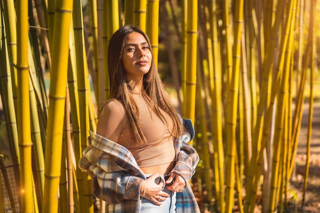 Autumn lifestyle in a bamboo forest, young caucasian brunette girl in a plaid wool sweater, looking to the left