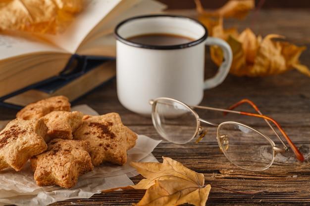 秋のライフスタイル-ホットチョコレート、チョコレートチップクッキー、古い本、暖かい毛布、素朴な木材の背景、