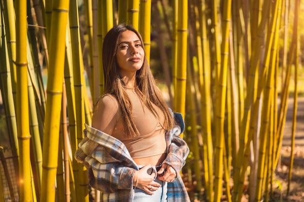 Осенний образ жизни в бамбуковом лесу, молодая кавказская брюнетка в клетчатом шерстяном свитере смотрит налево