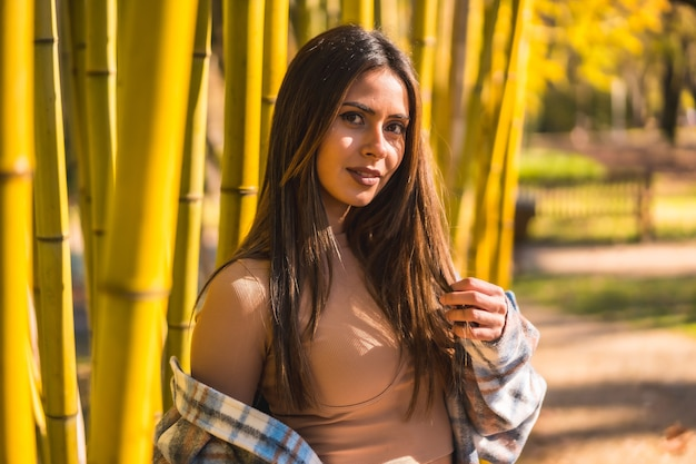Autumn lifestyle, young caucasian brunette girl in a plaid wool sweater in a bamboo forest