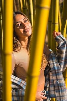 Осенний образ жизни, молодая кавказская брюнетка в клетчатом шерстяном свитере за бамбуком позирует в моде