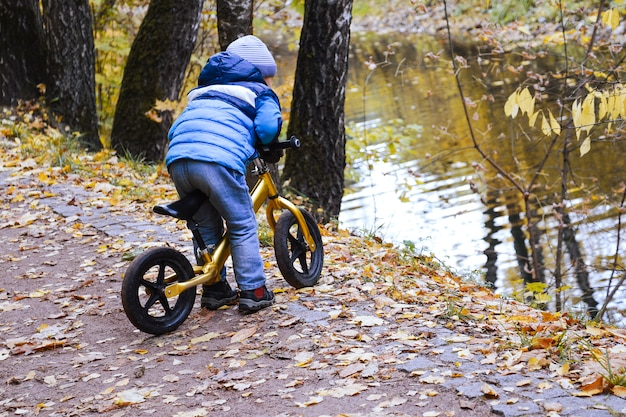 Autumn. a little boy rides a bike along a path in the park near the river. he rides on the edge of the cliff.