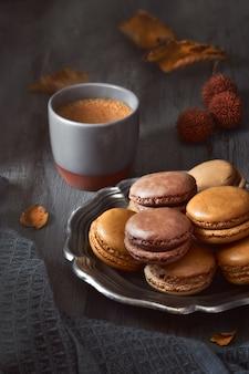 Autumn macarons with coffee on dark rustic wood
