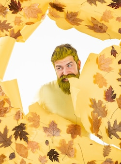 Autumn man playing with leaves and preparing for autumn sale. cheerful autumn man in park on isolated background. autumn happy people.