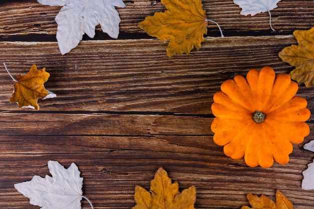 Autumn, maple, dry, yellow leaves, pumpkin, on an old wooden background with copy space.