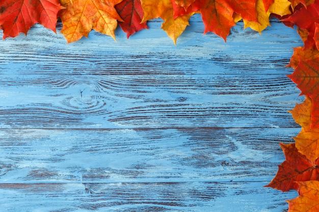 Осенний кленовый лист на синий деревянный стол. осень фон с копией пространства