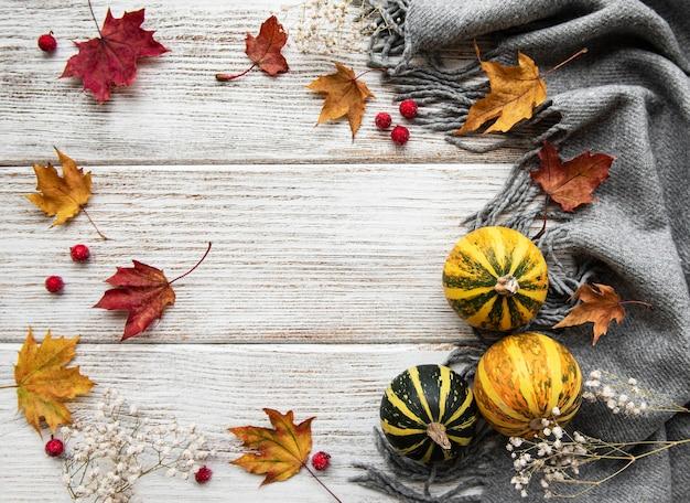 Осенние кленовые листья, тыквы и шерстяной шарф на деревянном фоне. осенний фон.