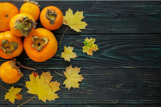 Autumn maple leaves and ripe persimmons on a textured wooden background