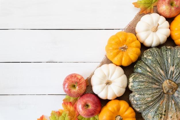 白い木製の背景にカボチャとリンゴと秋の葉が残っています。感謝祭のコンセプト