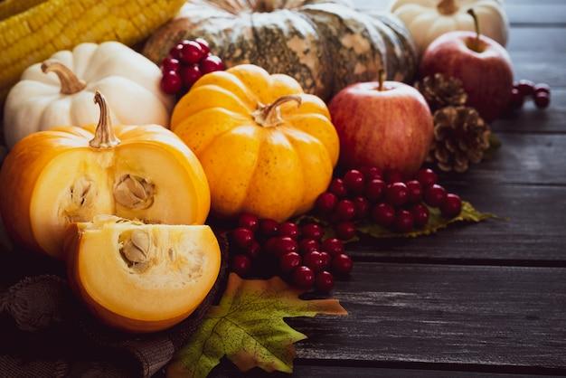 秋のカエデはカボチャと古い木製の背景に赤い果実と葉。感謝祭の共同