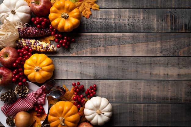 Autumn maple leaves with pumpkin, corn and red berries