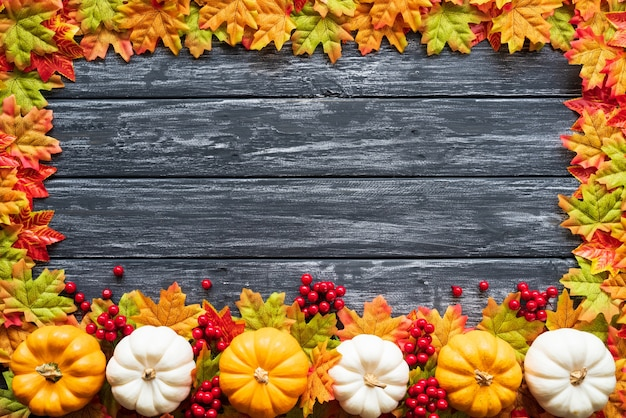 Autumn maple leaves with pumpkin and red berries on old wooden background.