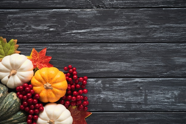Autumn maple leaves with pumpkin and red berries on old wooden.