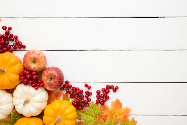 Autumn maple leaves with pumpkin and red berries on wooden background. thanksgiving concep