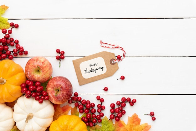 Autumn maple leaves with pumpkin and red berries on wooden background.