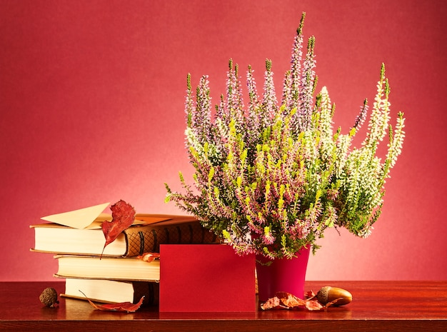 가을 메시지. 빨간색 빈 카드, 봉투, 헤더 꽃, 마른 잎과 책이 있는 정물