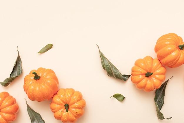 秋の最小限の構成。秋、秋、感謝祭、ハロウィーンのコンセプト。カボチャと黄色の背景。上面図、フラットレイ