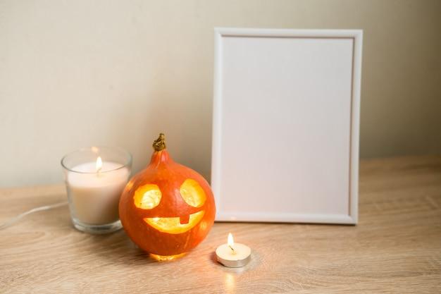 秋の最小限の構成。感謝祭の休日のコンセプト。フォトフレーム、白い背景の上のカボチャ。正面図、コピースペース。高品質の写真