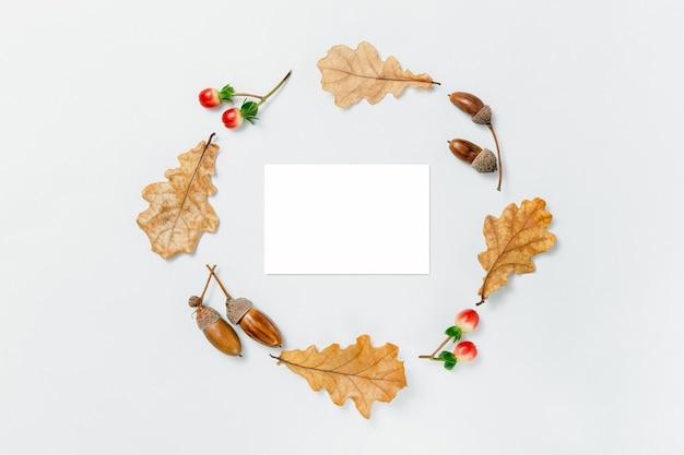 秋の最小限の構成。どんぐりの花輪、金色のaokの葉、白い背景の上の赤いベリー。テキストの秋のモックアップ。秋のデザイン要素、フラットレイ、上面図、コピースペース