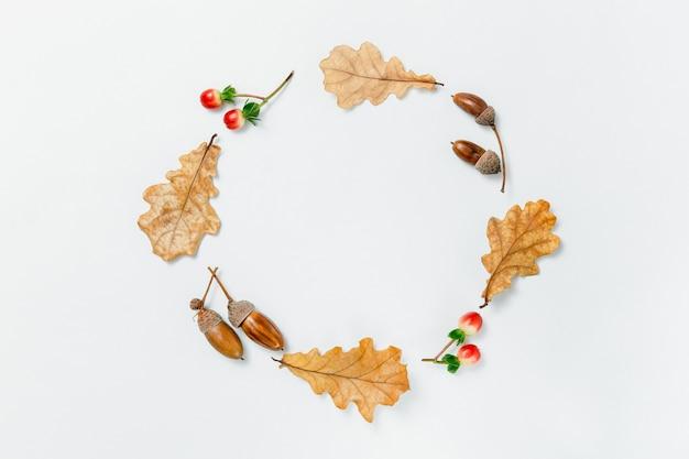 秋の最小限の構成。どんぐりの花輪、金色のaokの葉、白い背景の上の赤いベリー。テキストの秋のモックアップ。秋のデザイン要素、フラットレイ、上面図。