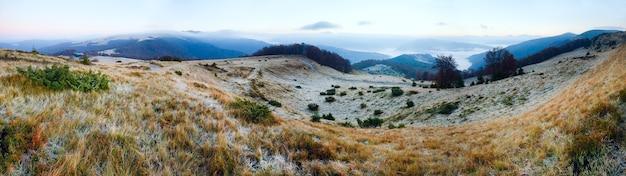 田舎道と牛小屋(カルパティア、ウクライナ)と秋の霧の朝の山のパノラマ。 4ショットステッチ画像。