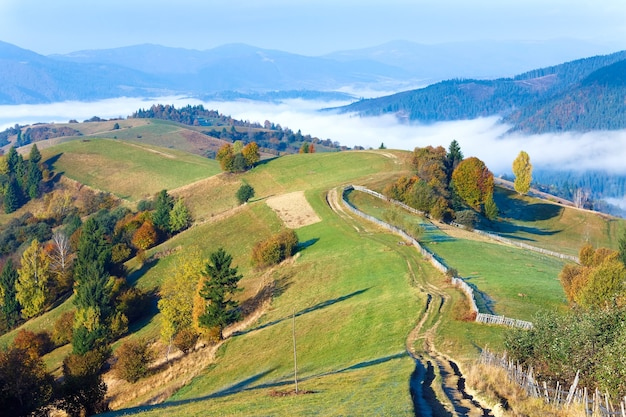 Осенний туманный вид на горы утром и проселочная грязная дорога (окраина села mighgirya, карпатские горы, украина).