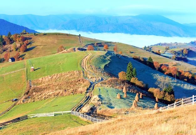 干し草の山と田舎の汚れた道のある秋の霧のかかった朝の高原(mighgirya村の郊外、カルパティア山脈、ウクライナ)。