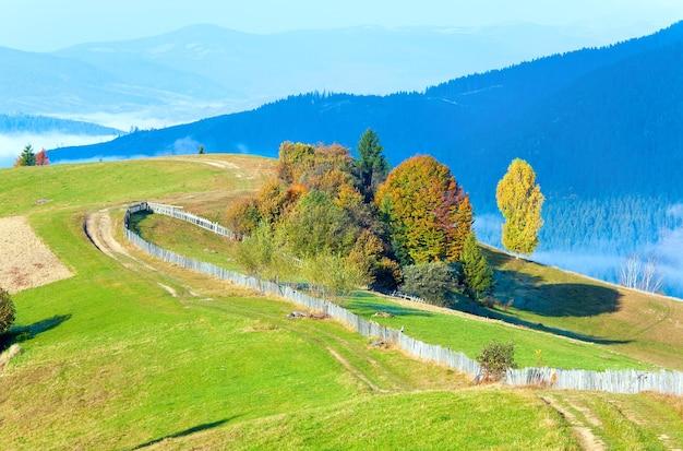Осеннее туманное утреннее плато со стеком сена и проселочной грязной дорогой (окраина села миггорья, карпатские горы, украина).