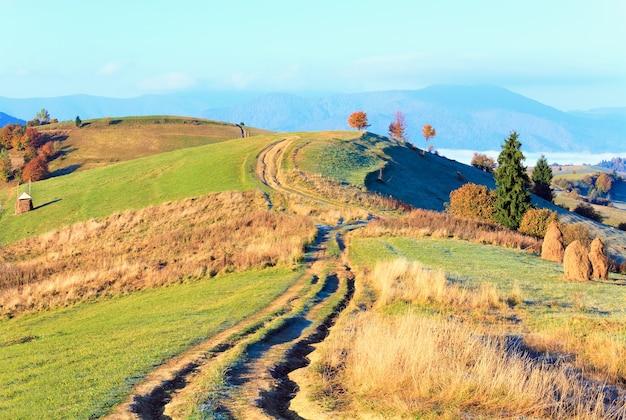 Осеннее туманное утреннее плато со стогом сена и проселочной грязной дорогой (окраина села миггорья, карпатские горы, украина).