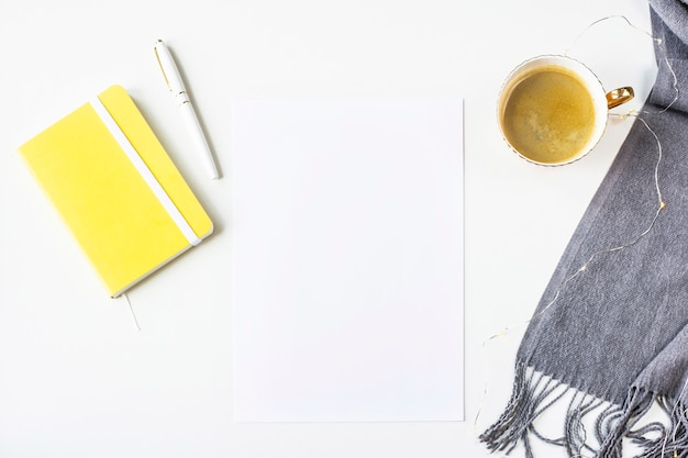 Autumn mock up on a white table next to a scarf, yellow notepad