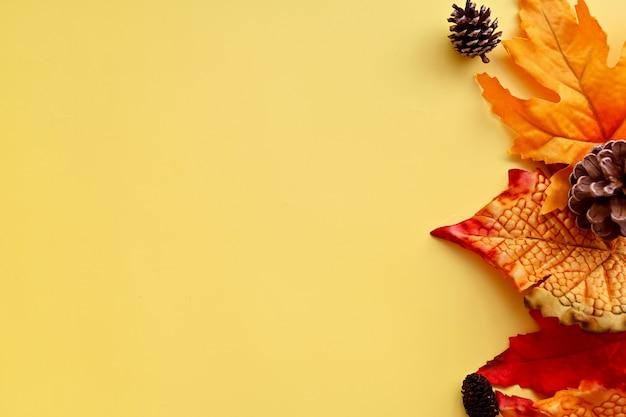 Осенний макет границы с оранжевыми осенними листьями, сосновыми шишками на ярком фоне, копией пространства для текста