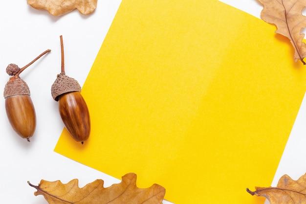 Осенняя рамка-макет из чистого листа бумаги. желтая рамка для текста. желуди и золотые дубовые листья на белом фоне. осенняя или осенняя концепция. осенний яркий фон, копия пространства.