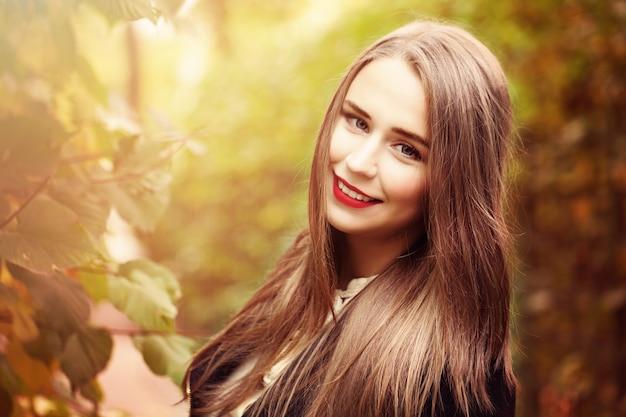 屋外の秋の公園で長い茶色の髪を持つ秋のモデルの女性