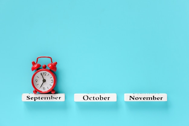 Autumn months and red alarm clock