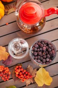 カボチャ、ナナカマドと葉と灰色の木製のテーブルの上の秋の気分の構成。お茶用の乾燥サンザシとガラスのオープンジャー。
