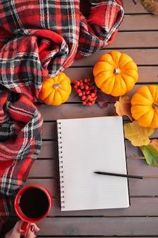 カボチャのナナカマドと葉と木製のテーブルの上の秋の気分の構成。赤いカップと灰色の木製テーブルでメモ帳とブラックコーヒーを開きます