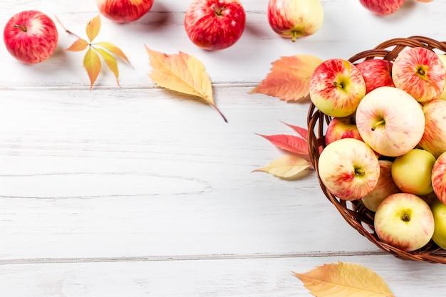 Осеннее настроение с красными яблоками в плетеной корзине и желтыми листьями