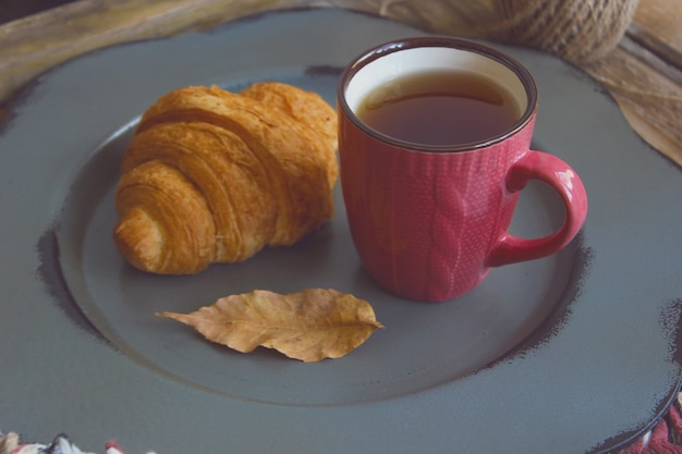 Autumn mood french breakfast composition cup of tea and croissants