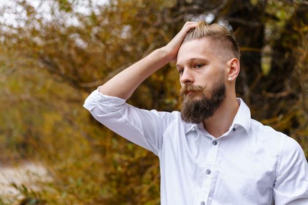 白いシャツを着た秋の気分の物思いにふける若い男は、beaを背景に公園を瞑想して歩きます...