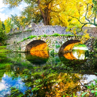 Autumn mood, scenery with roman bridge in ninfa park, italy