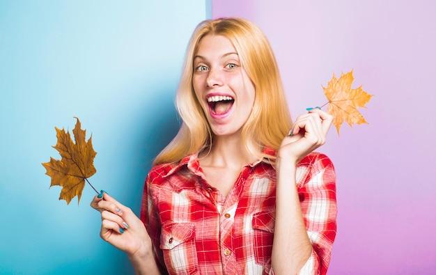 Осеннее настроение улыбающаяся женщина с кленовыми листьями модные тенденции на осень счастливая девушка с желтыми листьями
