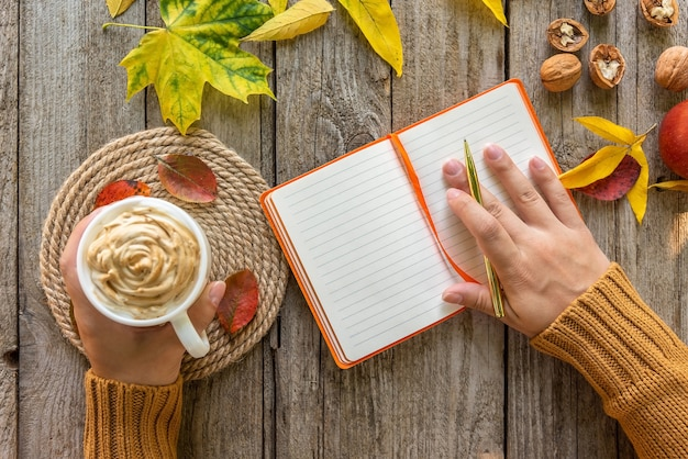 On an autumn morning, a girl makes notes in a notebook.