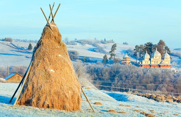 Осенний утренний иней на пастбище на окраине горной деревни и стоге сена