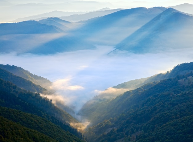Осеннее утро с видом на горы с солнечным лучом и дымкой